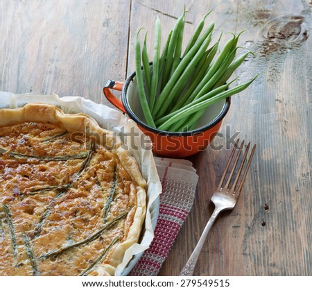 Homemade vegetable tart with green beans on wooden table - stock photo