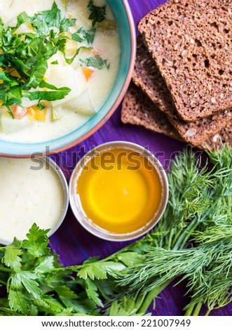 Homemade vegetarian soup with potato, carrots, pepper  with dark bread and dill on wooden background - stock photo