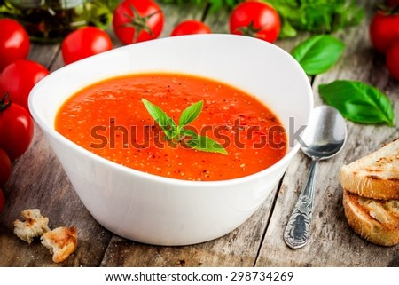 homemade vegetarian tomato cream soup in white bowl on wooden table - stock photo