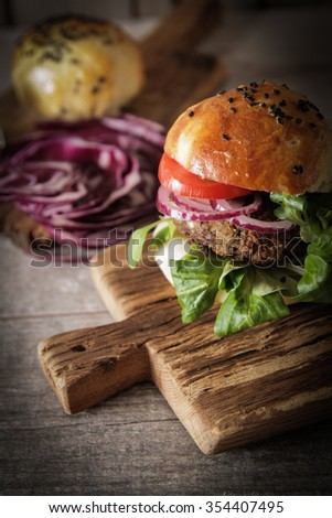 homemade veggie burger in a bun with sesame seeds of beer. delicious fast food for vegans. on a wooden background - stock photo
