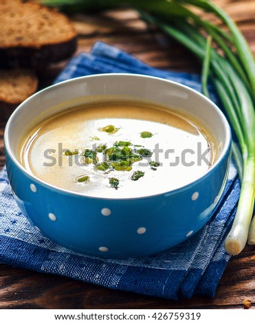 Homemade vichyssoise cream soup served with chives, in blue bowl on wooden table. Potato and Leek Soup. - stock photo