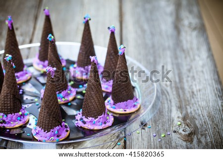 Homemade waffle cones cookies in the form of a Halloween witch hat decorated with purple icing on a wooden background. Selective focus on the hat. Also available in vertical format.   - stock photo