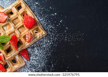 Homemade Waffles with fresh Strawberries (on dark background) - stock photo