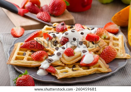 Homemade waffles with maple syrup and strawberries, topped cream and chocolate chips, orange fresh beverage - stock photo