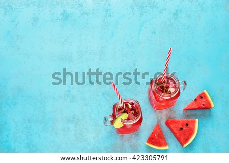 Homemade watermelon lemonade in mason jar with red striped straw and slices of watermelon on a blue background - stock photo