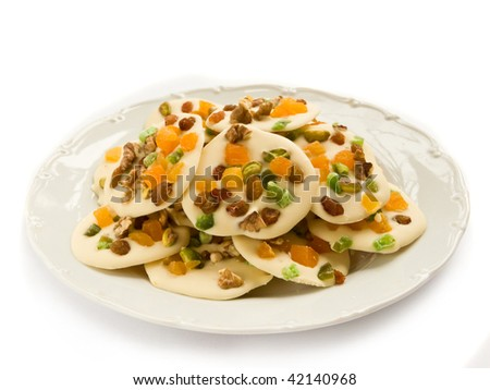 Homemade white chocolate cookies decorated with dried apricots, pistachios, raisin, candied fruits and walnuts, isolated over white. - stock photo