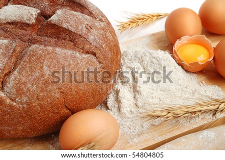 Homemade whole bread and flour on a white background - stock photo