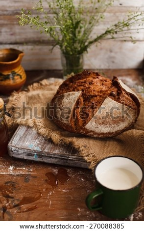Homemade whole bread with pottery pitcher of milk. Natural local food. Rustic style. - stock photo