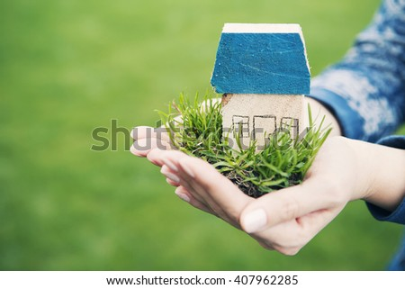 Homemade wooden house with green grass in the hands of women on a background of green grass, side view