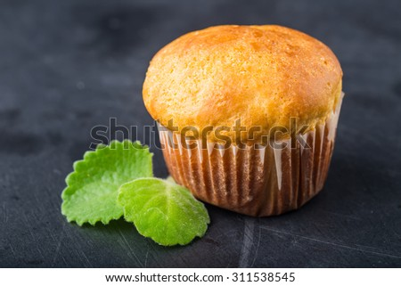 Homemade yeast bun on black wooden table, studio shot - stock photo