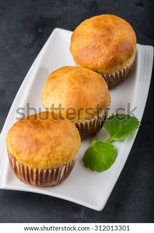 Homemade yeast buns on white plate, on black table - stock photo