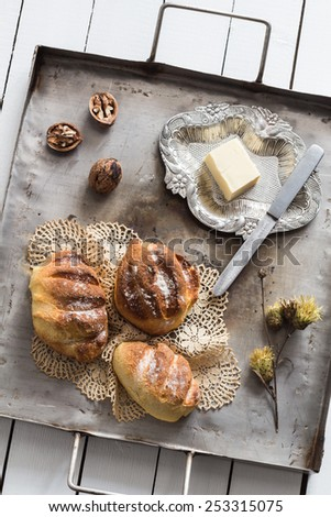 Homemade Yeasted Honey Cornbread Loaves, Butter, Walnuts and Dried Flowers on a Vintage Tray - stock photo