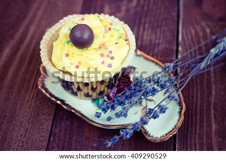 Homemade yellow cupcake decorated with sweet icing and chocolate berry on wooden hand painted background. - stock photo