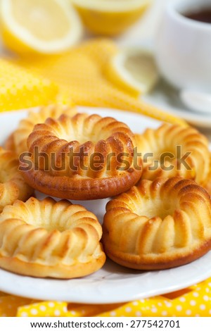Homemade yellow lemon cakes and cup of tea. Selective focus. - stock photo