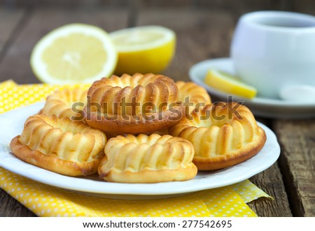Homemade yellow lemon cakes on wooden table. Selective focus. - stock photo