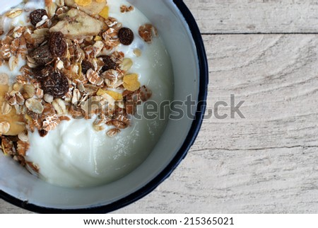 homemade yoghurt with muesli and banana on wooden table.   - stock photo