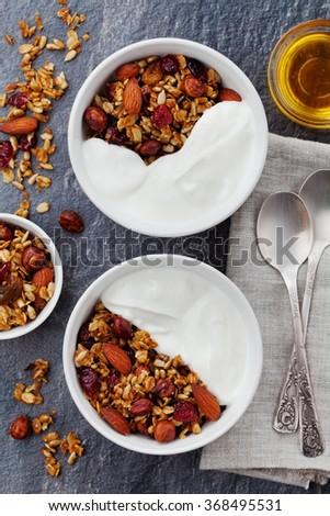 Homemade yogurt bowl with granola on black kitchen table, healthy and diet breakfast, top view - stock photo