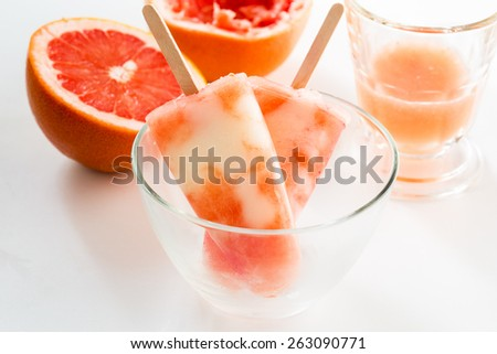 Homemade yogurt ice pops with fresh grapefruit juice  for hot summer days on a white table - stock photo