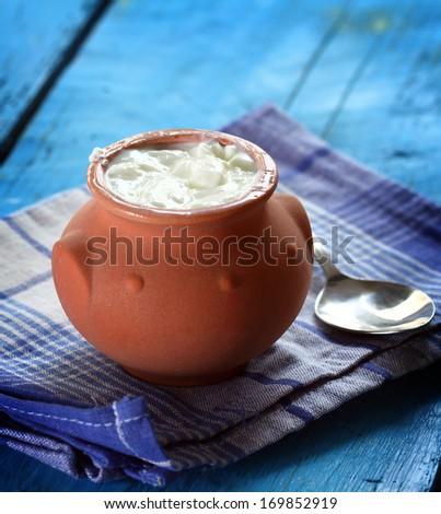 Homemade yogurt in a ceramic pot and spoon - stock photo