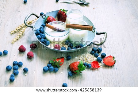Homemade yogurt in a jar with strawberry and cinnamon , granola with blueberry ,organic food ,rustic lifestyle - stock photo