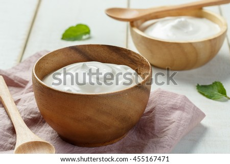 Homemade yogurt or sour cream in a wooden bowl - stock photo