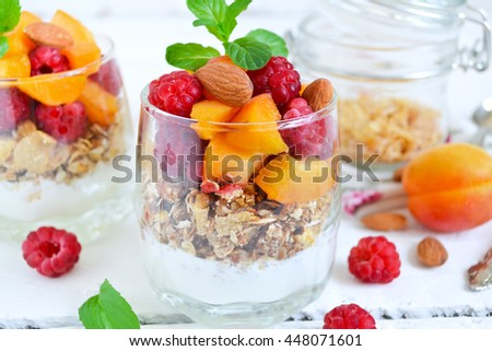 Homemade yogurt with granola apricots, peaches and raspberries on a white background