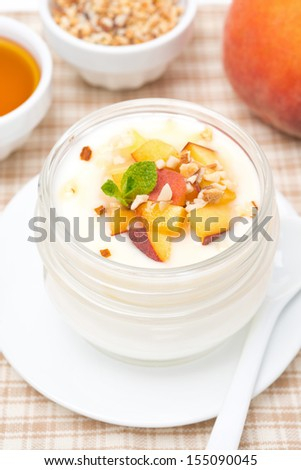 homemade yogurt with honey, peaches and nuts, top view, vertical - stock photo