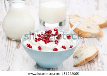 homemade yogurt with pomegranate, milk and bread on the wooden table - stock photo
