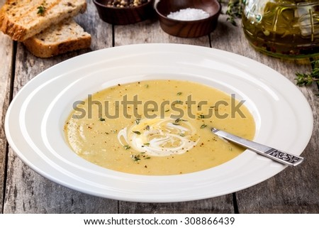 homemade zucchini cream soup  in white plate on wooden background - stock photo