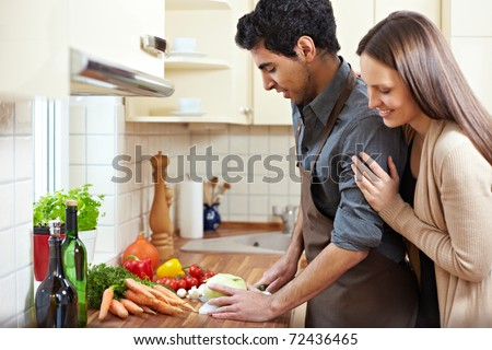 Homemaker preparing lunch while happy woman is watching him