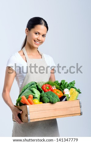 Homemaker woman chef holding a wooden crate full of fresh raw organic produce vegetables - stock photo