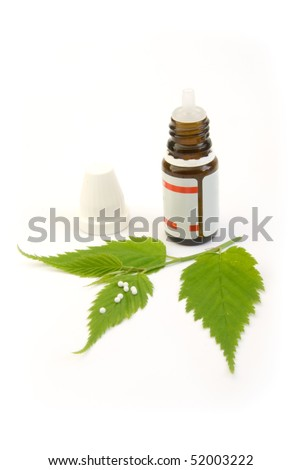homeopathic globule pills and leaf isolated on white