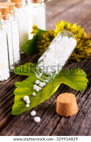 Homeopathic lactose sugar globules on leaf with glass bottle - stock photo