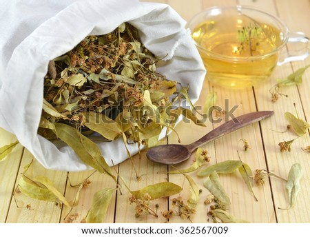 Homeopathic medicine and healthcare still life of dried flowers and leaves of linden in white textile bag and cup of herbal tea over wooden surface background - stock photo