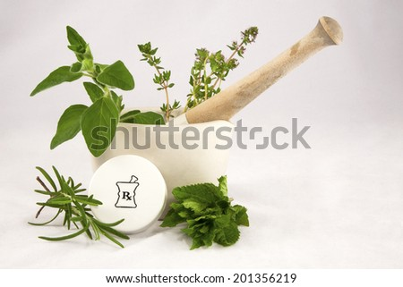 Homeopathic medicine concept of mortar and pestle containing fresh herbs with a prescription vial cap - stock photo