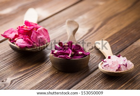 Homeopathic medicine, rose dry flowers and wooden surface. - stock photo