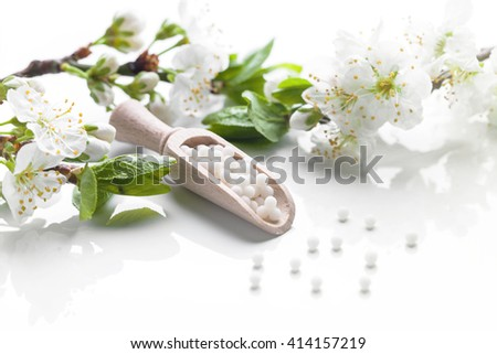 homeopathic pills with spring flowers on white background - stock photo