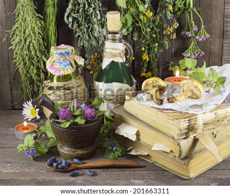 Homeopathic still life with healing herbs, books, glassware and candles - stock photo