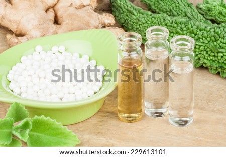 Homeopathy - A homeopathy concept with homeopathic medicine (sugar/lactose pills and liquid homeopathic substances) pictured along with homeopathic vegetables and herbs on a wooden tabletop. - stock photo