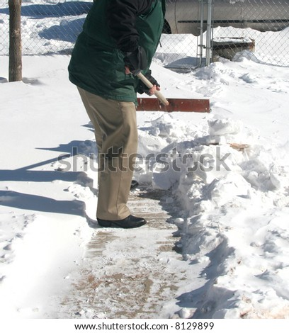 Homeowner shoveling snow on front walkway after winter storm to get to snow-covered driveway. - stock photo