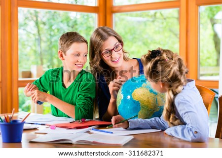 Homeschooling mother teaching kids private lessons in geography - stock photo
