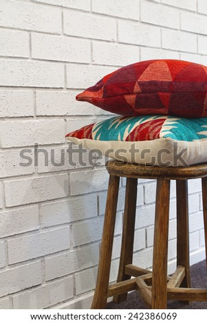 Homewares decorator cushions on a rustic wooden stool - stock photo