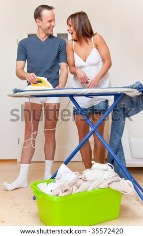 Homework couples while housekeeping and ironing the clothes while laughing - stock photo