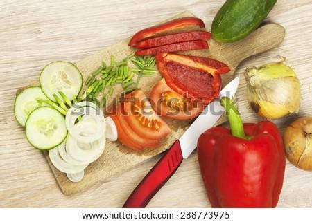 Homework vegetable salad. Ceramic paring knife. - stock photo