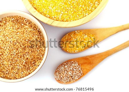 Hominy and wheat grits in wooden plates - stock photo