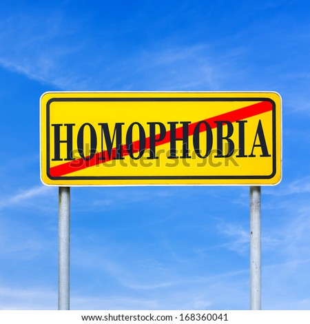 Homophobia written on yellow street sign and crossed off. Stop homophobia concept. - stock photo