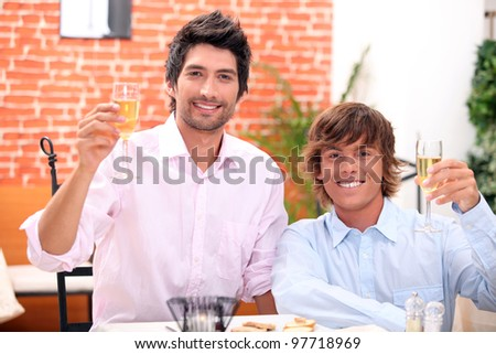 homosexual couple celebrating event at restaurant - stock photo