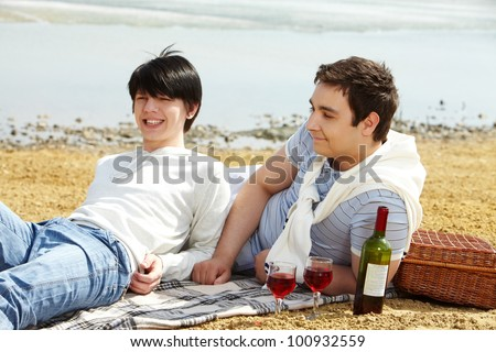 Homosexual couple enjoying themselves having a picnic at seaside - stock photo