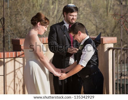 Homosexual couple holding hands with rabbi officiating - stock photo