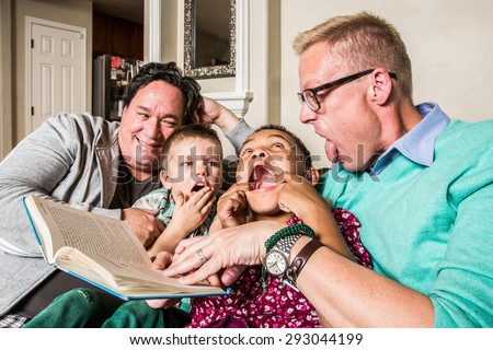 Homosexual parents reading and making faces with son and daughter - stock photo